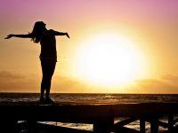 woman celebrating sunset
